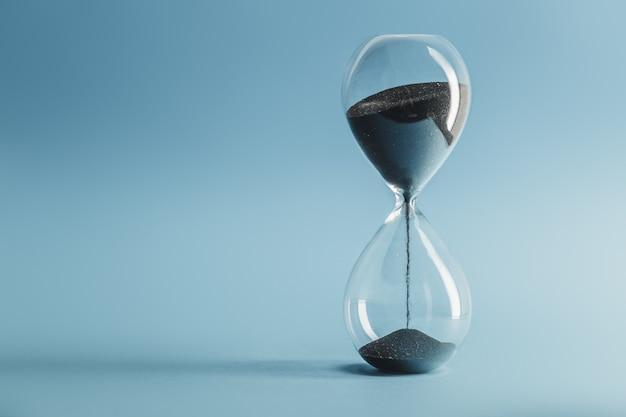 Hourglass on blue Premium Photo
