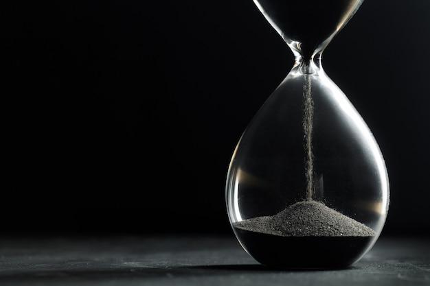 Hourglass on dark background Premium Photo