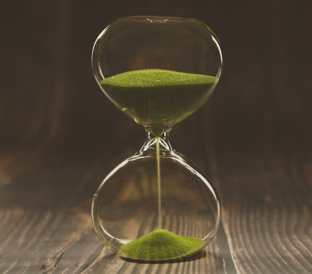 Hourglass on dark wood Premium Photo