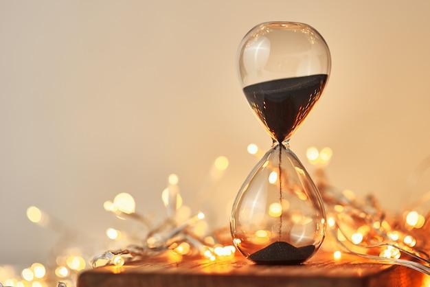 Hourglass and festive garland lights in bokeh Premium Photo