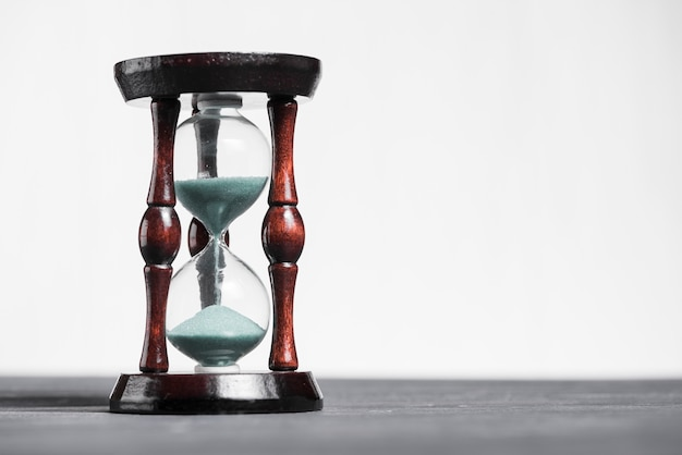 Hourglass on grey desk showing the last second or last minute or time out Free Photo