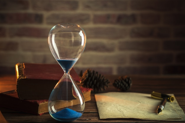 Hourglass and old books with old paper and pen on wooden tables in lighting of the lantern. Premium Photo