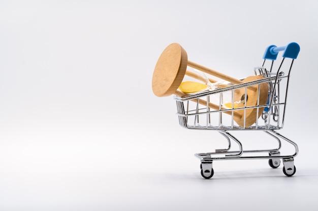 Hourglass in shopping cart on white Premium Photo