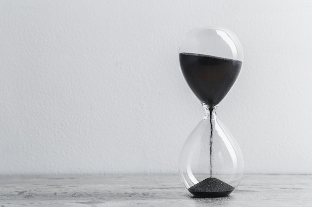 Hourglass on table with white background Premium Photo