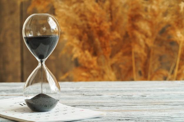 木製の机のカレンダーと砂時計。時間の概念 Premium写真