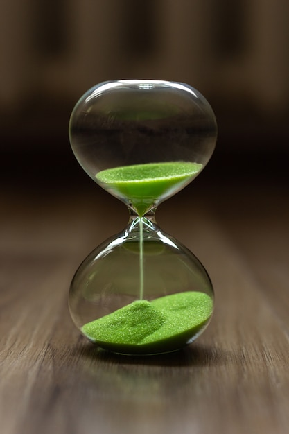 Hourglass with green sand on a blurred background Premium Photo