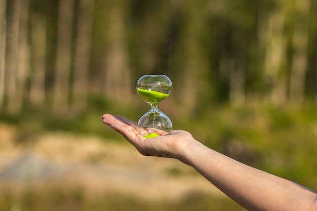 Hourglass with green sand on the palm of the girl on a blurred background Premium Photo
