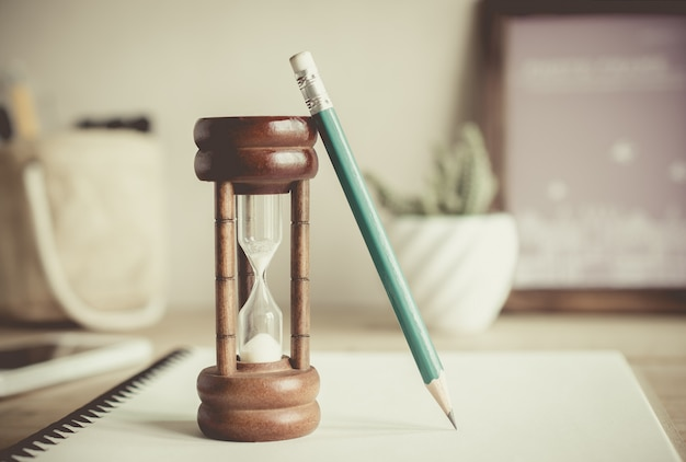 Hourglass with pencil on notebook, time passing concept Premium Photo