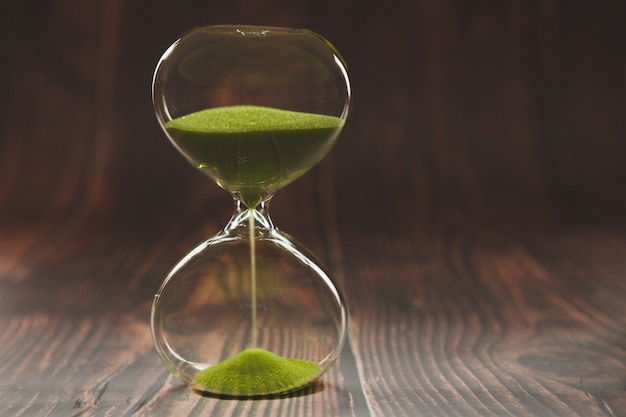 Hourglass on wooden boards. Premium Photo