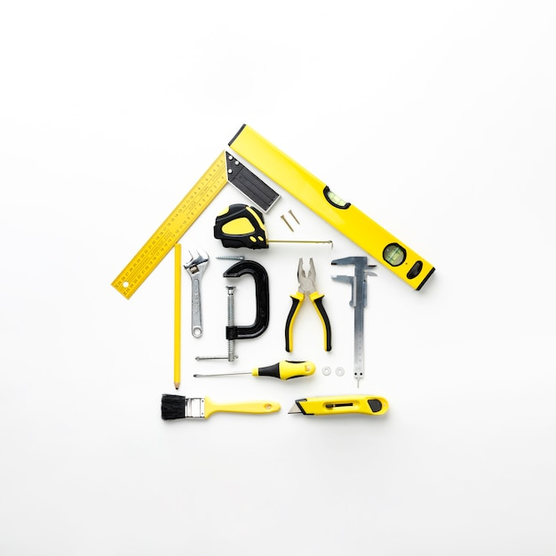 House arrangement from yellow repair tools flat lay Free Photo