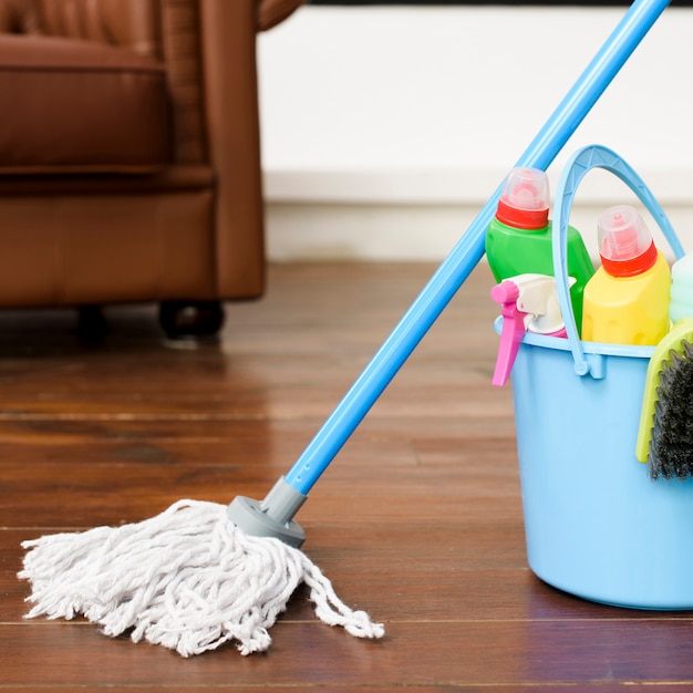 House cleaning products in blue bucket on hardwood floor Premium Photo