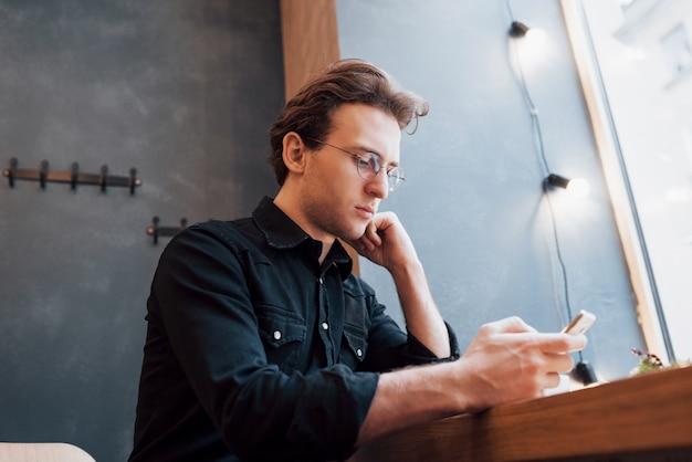 携帯電話を操作している若者のためのモダンなhouse.conceptでソファに座って、リラックスしてphone.whileを押しながら使用するソフトfocus.man Premium写真