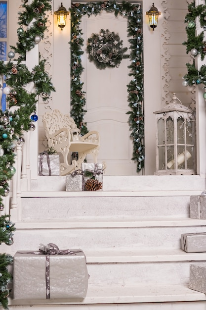 House entrance decorated for holidays.garland of branches and lights on the railing.festively decorated house. lantern, gift boxex in silver.holiday postcard Premium Photo
