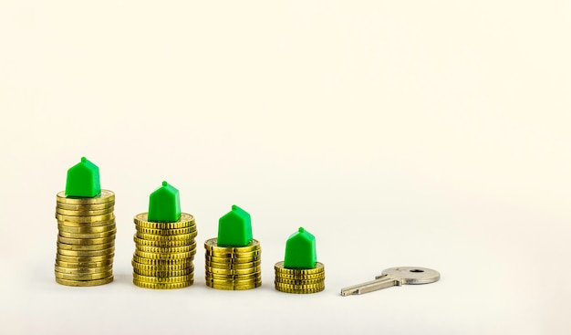 House key and mini houses about the coins, real estate investment, save money with stack coins Premium Photo