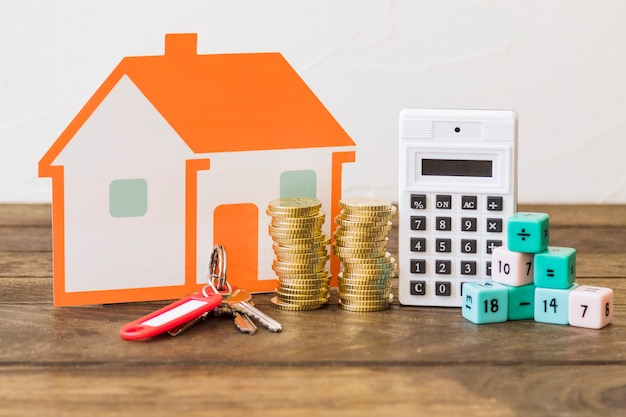House, key, stacked coins, calculator and math blocks on wooden table Free Photo