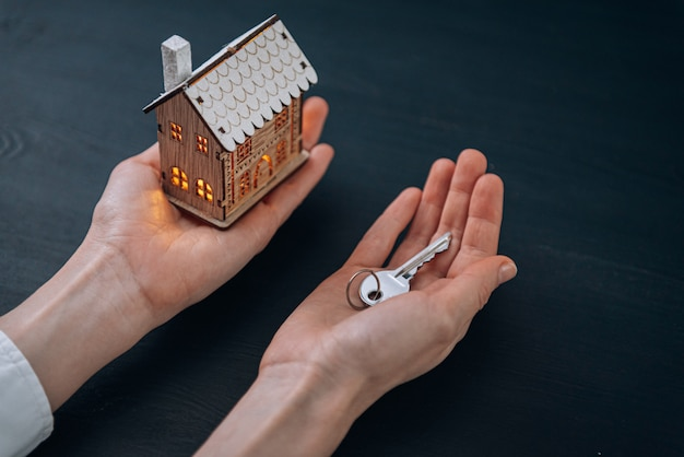 House keys in the hands of a woman and a small model of a house with luminous windows nearby. concept of acquiring your home Premium Photo