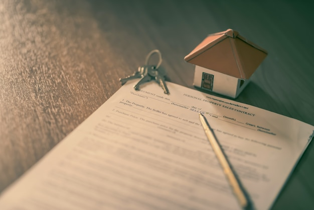 House keys on the rental agreement or the buy home contracts with the real estate property background. Premium Photo