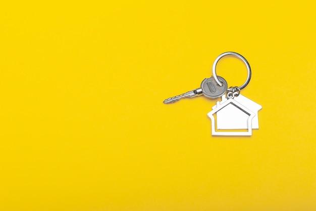 Расквартируйте ключи с побрякушкой на предпосылке цвета, взгляд сверху с космосом экземпляра. ключ от дома на желтом фоне. минимальный стиль плоской планировки с местом для текста. Premium Фотографии