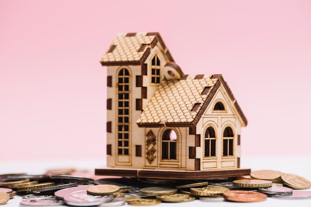 House model over coins in front of pink background Free Photo