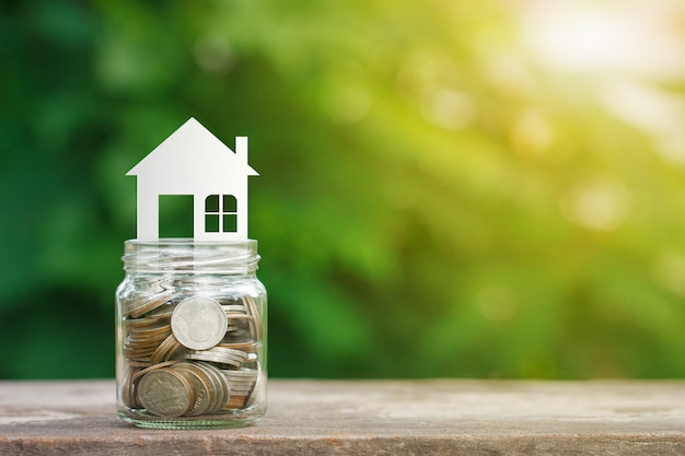 House model on coins in glass jar, saving to buy a house Premium Photo