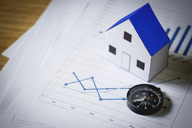 House model and compass on plan background, real estate concept Free Photo