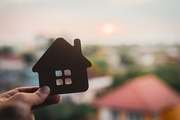 House model in home insurance broker agents hand or in salesman person. Premium Photo