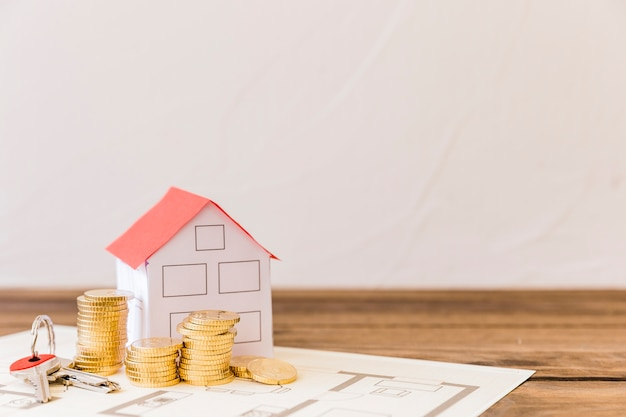 House model, key and stacked coins on blueprint Free Photo