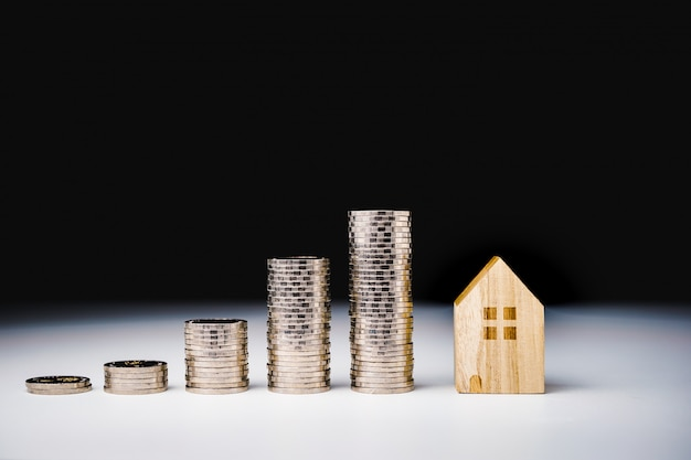 House model and row of coin money on white table Premium Photo