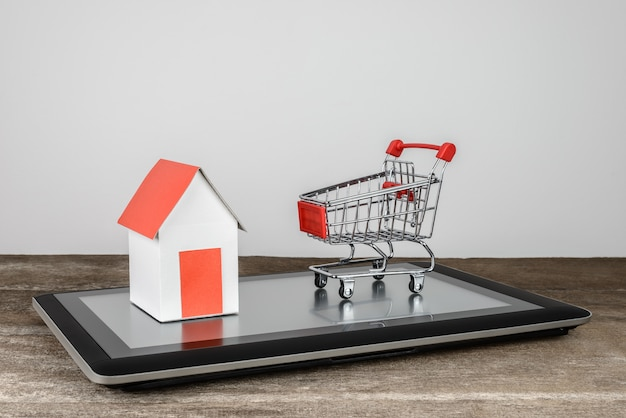 House model and shopping cart on tablet Premium Photo
