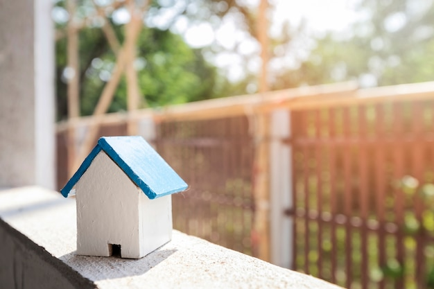House model on window frame in housing construction site. Premium Photo