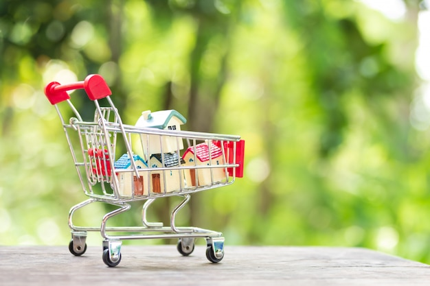 House models stacking on shopping cart. concept for property ladder Premium Photo