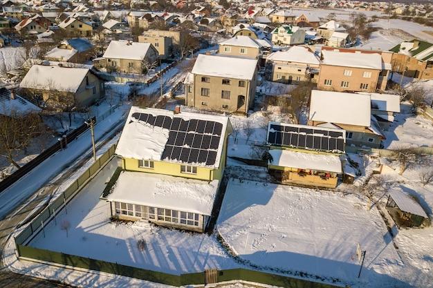 Dach domu pokryty panelami słonecznymi zimą ze śniegiem na górze Premium Zdjęcia