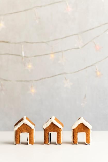 집 모양의 진저 쿠키. Garlands 배경에 3 개의 진저 하우스입니다. 수직 프레임. 프리미엄 사진