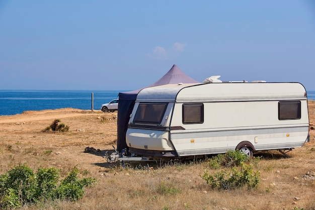 The house on wheels is parked on the wild beach. Premium Photo