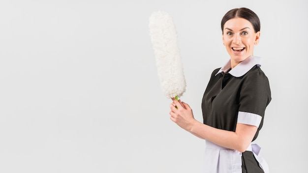 Housekeeper with happy surprised face and duster Free Photo