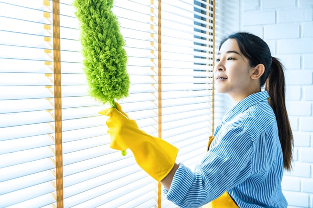 Housekeeping and cleaning concept, happy young woman in yellow rubber gloves wiping dust using feather broom while cleaning on window at home Premium Photo