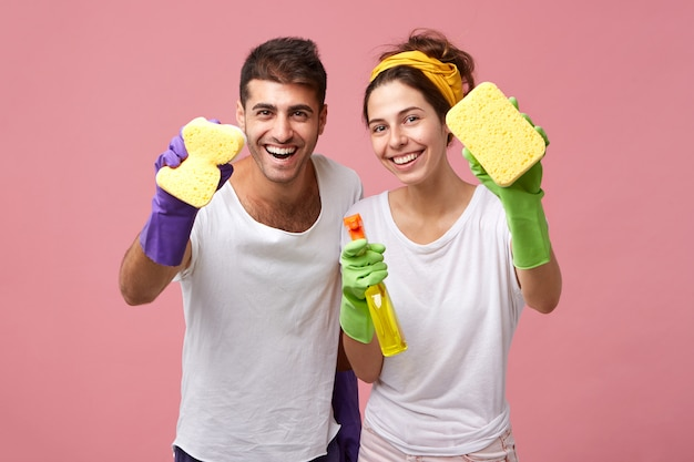 Housekeeping, cleanliness, hygiene and domestic work concept. happy caucasian young family in protective rubber gloves using detergent and rags while tidying up in the kitchen together on weekend Free Photo