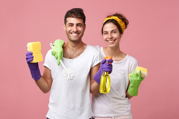 Housekeeping, domestic duties and teamwork concept. beautiful young european family sharing household chores: woman with sponge and toilet brush cleaning bathroom while man washing windows with spray Free Photo