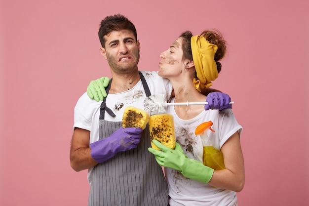 La domestica in abiti casual e guanti protettivi va a baciare il marito che ha l'aria stanca ed esausta Foto Gratuite