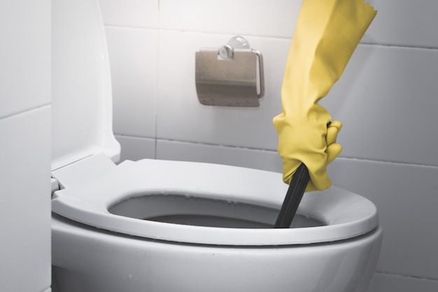 Housemaid wearing yellow rubber glove and using brush cleaning in the toilet Premium Photo