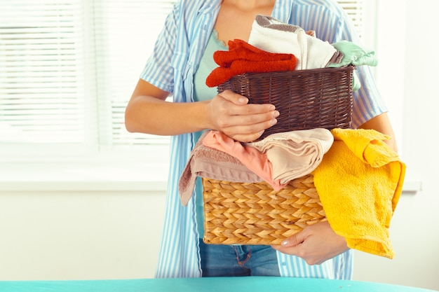 Housewife bringing a huge pile of laundry on the ironing board Premium Photo