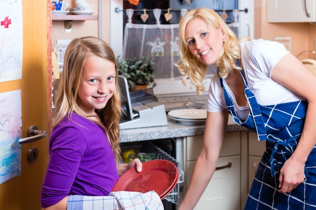 Housewife and daughter doing dishes with dishwasher Premium Photo