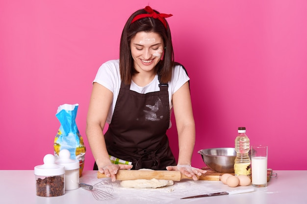 Housewife happily kneads dough with rolling pin. Free Photo
