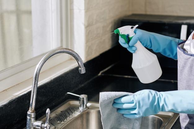 Домохозяйка распыляет кухонный кран Premium Фотографии