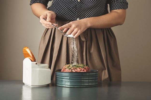 주부 인식 할 수없는 여자는 파란색 테이블에 세라믹 그릇에 다진 고기에 약간의 소금을 추가 무료 사진
