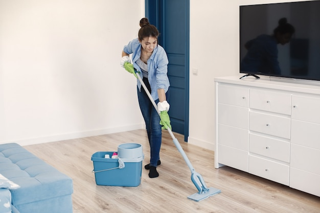 집에서 주부 워킹. 파란 셔츠에있는 여자. 여자 깨끗한 바닥. 무료 사진