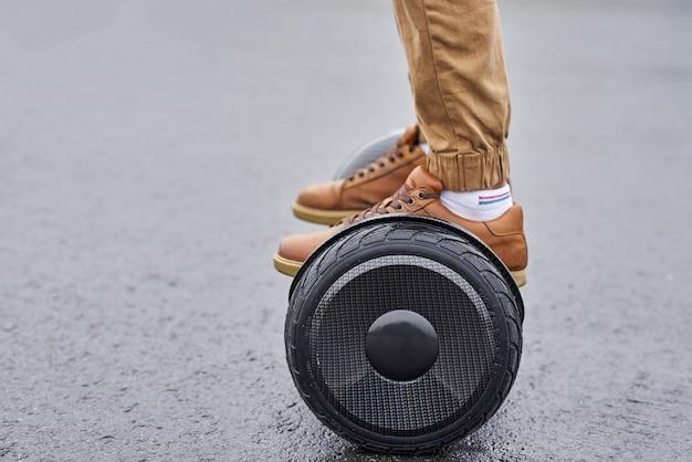 Закройте вверх человека используя hoverboard на дороге асфальта. ноги на электрический скутер открытый Premium Фотографии