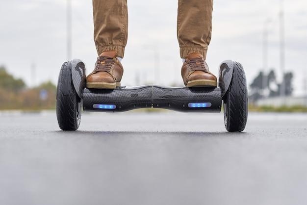 Закройте вверх человека используя hoverboard на дороге асфальта. Premium Фотографии