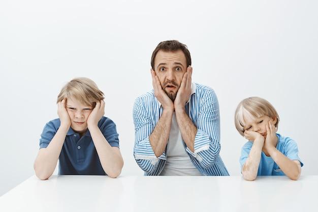 彼らがいかに早く育ったか。息子と一緒に座っている、顔に手を繋いでいると顎を落としているショックを受けた不安なヨーロッパの父の肖像 無料写真