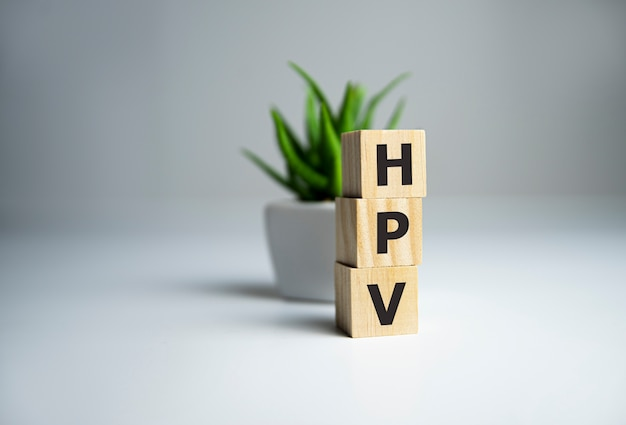 Hpv word written with wood block next to plant